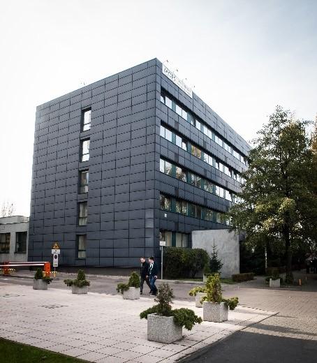 Czteropiętrowy budynek w ciemnoszarym kolorze.