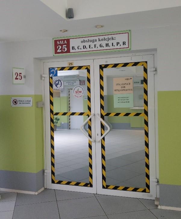 Zdjęcie drzwi do pokoju 25. Drzwi są dwuskrzydłowe, lustrzane. Drzwi są oklejone dookoła żółto-czarną taśmą.